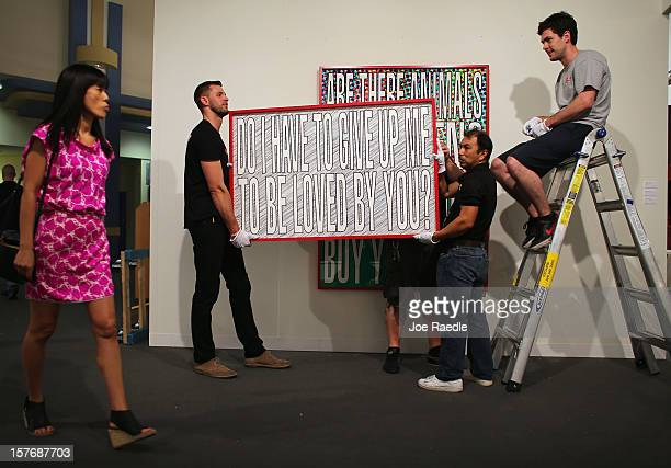 Workers from Safe Art Transport company place a piece of art of the wall of L&M Arts Gallery as Art Basel opens at the Miami Beach Convention Center...