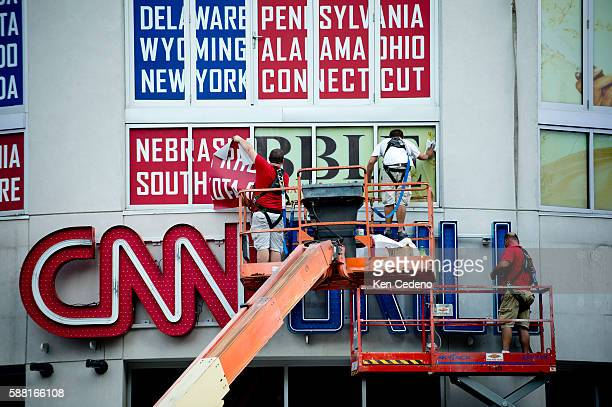 Workers from SignArt paste posters above the CNN Grill sign at the EpiCentre in Charlotte NC August 31 2012 just days prior to the Democratic...