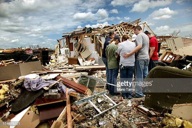 Workers from Skaggs Chiropractic hold a group prayer outside their destroyed office after a massive tornado passed through the town killing at least...