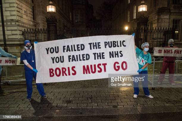 Workers from St Thomas's Hospital, including ICU staff, hold up a sign telling Prime Minister Boris Johnson he 'must go' during a protest at the...