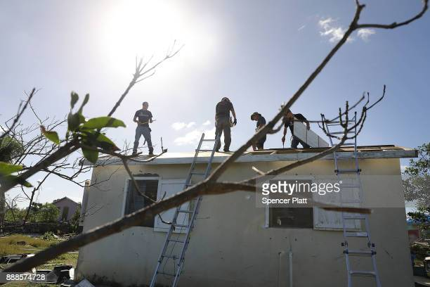 Workers from the charity Samaritan's Purse place a new roof on a home on the nearly destroyed island of Barbuda on December 8, 2017 in Cordington,...
