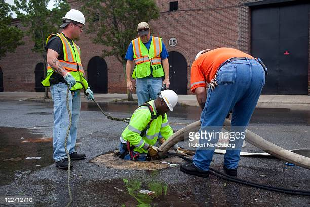 Workers from the Department of Environmental Protection adjust a drainage hose in the sewer system August 28 2011 in the Brooklyn borough of New York...