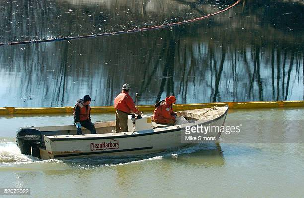 Workers from the EPA and Sunoco drive past a boom on the Kentucky River after an oil spill January 27 2005 in Carrollton Kentucky An estimated 63000...