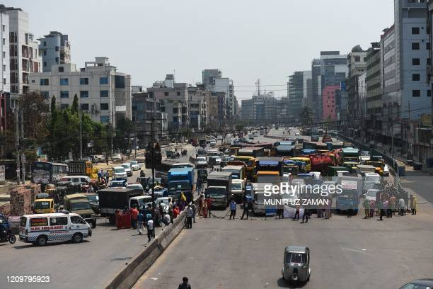 Workers from the garment sector block a road during a protest to demand payment of due wages, in Dhaka on April 13, 2020. - Thousands of garment...