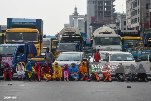 Workers from the garment sector block a road during a protest to demand payment of due wages, in Dhaka on April 15, 2020. - Thousands of garment...