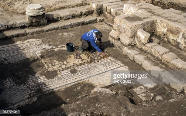 Workers from the Israeli Antiquity Authority clean a rare Roman mosaic from the 2nd3rd centuries at the Israeli Caesarea National Park on February 8...