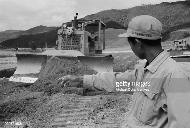 Workers from the Japanese Maruma Technica earthmoving equipment company work on a site in South Vietnam during the Vietnam War March 1962