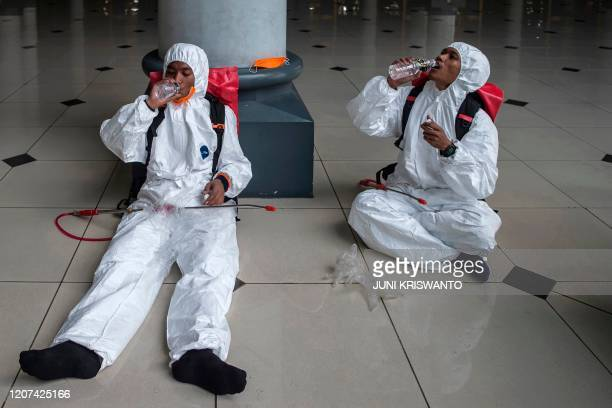 Workers from the local disaster management authority take a break after spraying disinfectant at a mosque in Surabaya, East Java, on March 17 amid...