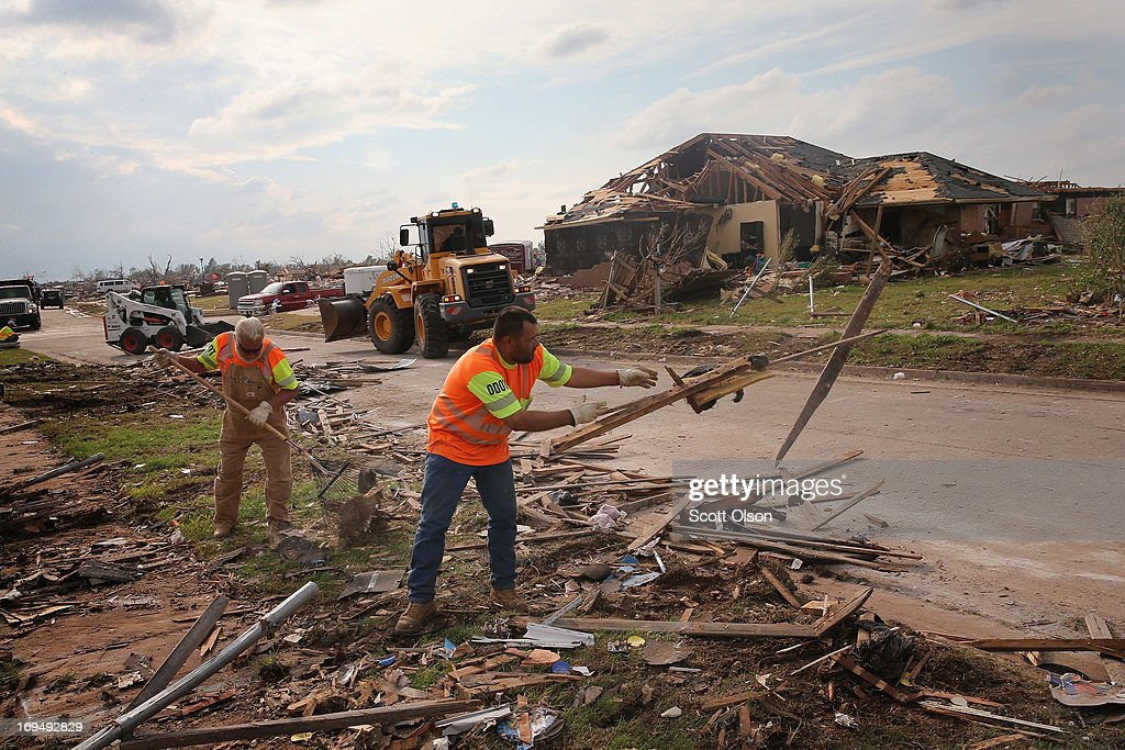 Workers from the Oklahoma Department of Transportation clear tornado debris that was piled along a street on May 25, 2013 in Moore, Oklahoma. A two-mile wide EF5 tornado touched down in Moore May 20 killing at least 24 people and leaving behind extensive damage to homes and businesses. U.S. President Barack Obama promised federal aid to supplement state and local recovery efforts.