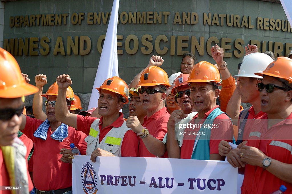 Workers from the Philippines' largest mining firm, Philex Mining, shout slogans outside the offices of the Mines and Geosciences Bureau in Manila February 6, 2013 as pigs (not pictured) are slaughtered as part of a religious sacrifice. The workers, who are from an indigineous tribe hoped the ceremonial offering would help convince the government to reopen the Padcal gold mine of the Philex Mining Corp. The company's main mining site in the northern mountain district of Padcal suffered a spill of mine waste or 'tailings' in August 2012 after the area was hit by two powerful typhoons, suspending operations at the mine since. AFP PHOTO / Jay DIRECTO