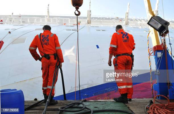 Workers from the Rotterdam based SMIT salvage firm works from a pontoon while taking part in the operation to remove fuel from the cruise ship Costa...