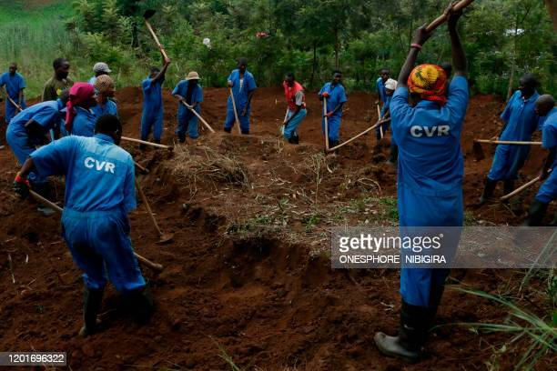Workers from the Truth and Reconciliation Commission using hoes dig at the site of a mass grave on February 18 2020 in Shombo Karusi Province north...