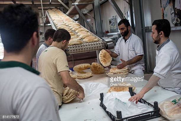 Workers from the Turkish Humanitarian Relief Foundation prepare bread made in the specially setup Syrian bakery for distribution to refugee camps...