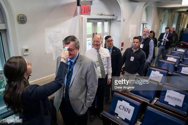 Workers from the White House Physician's Office check the body temperatures of journalists in the press briefing room at the White House on March 17...