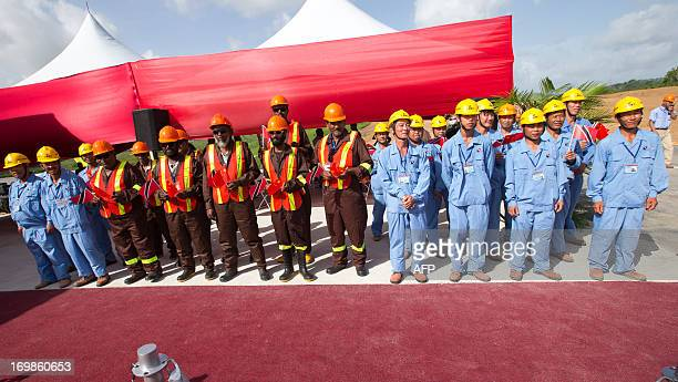 Workers from Trinidad & Tobago and China, wait for the arrival of Chinese President Xi Jinping at the site of the Couva Children's Hospital, in which...