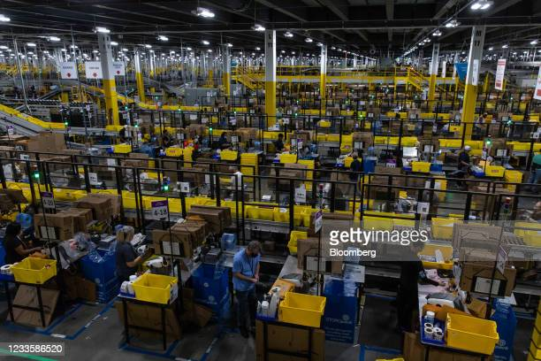Workers fulfill orders at an Amazon fulfillment center on Prime Day in Raleigh, North Carolina, U.S., on Monday, June 21, 2021. Amazon.com Inc.'s...