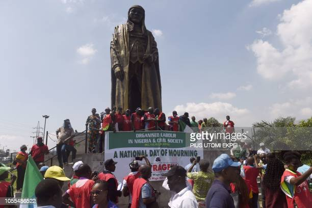 Workers gather around the statue of Nigerian social critic author and politican Gani Fawehinmi during a march to protest against the government's...