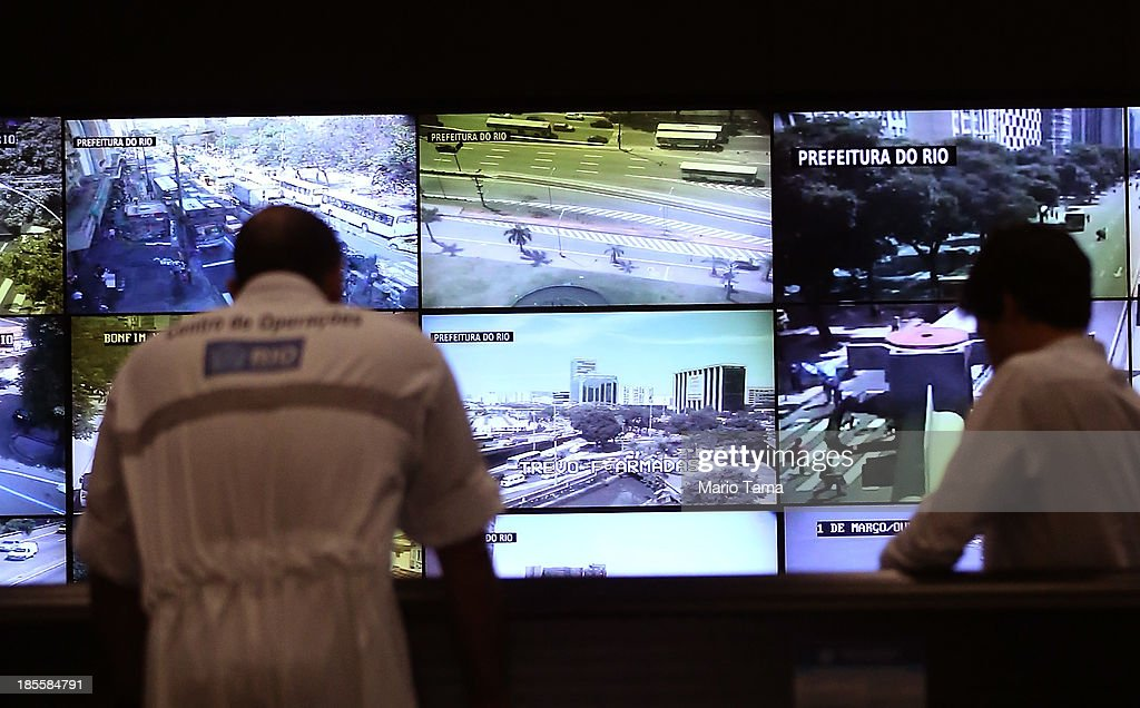 Workers gather in the Rio Operations Center which gathers data from 30 city agencies on October 22, 2013 in Rio de Janeiro, Brazil. The center boasts the largest video wall in Latin Amerca with 80 screens streaming feeds from 900 cameras and serves as a headquarters for the management of the city. Preparations are continuing for the Rio 2016 Olympic Games along with the 2014 FIFA World Cup in Brazil.