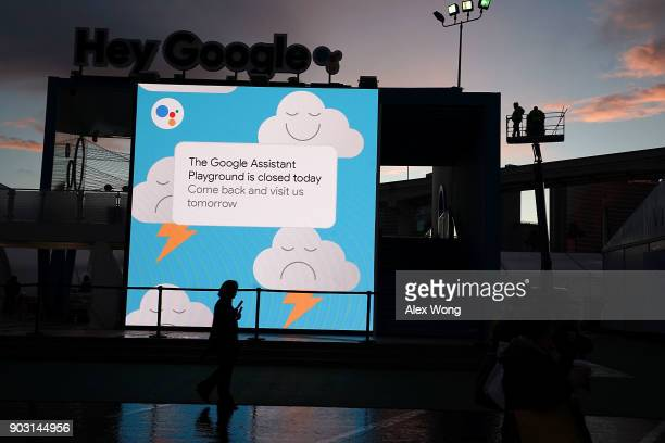 Workers get ready to clear up water collected on a tarp atop of the roof of the Google booth which was closed on the first day of CES 2018 at the Las...