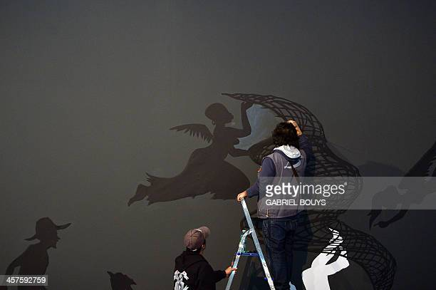 Workers give the final touch at a collage of black cutpaper by AfricanAmerican artist Kara Walker as part of the exhibition Non Basta Ricordare...