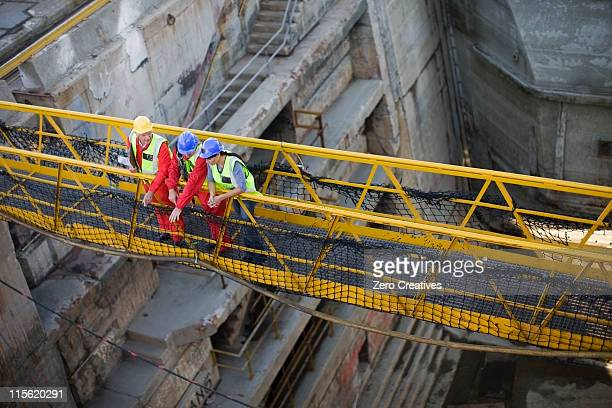 Workers going over bridge in dockyard