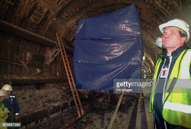 Workers guard the burned out Le Shuttle locomotive concealed by a tarpaulin inside the Channel Tunnel Tuesday Nov26 where fire broke in a truck on a...