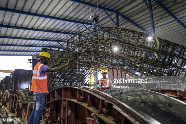 Workers guide the steel reinforcing frame of a precast concrete tunnel segment being maneuvered by crane to a mold at the Mumbai Metro Rail Corp...