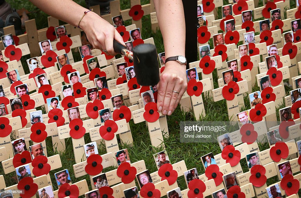 Workers hammer in crosses representing victims of the war in Afghanistan in the Field of Remembrance at Westminster Abbey on November 5, 2015 in London, England.