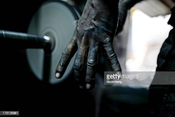A workers hand is seen as he makes a stainless steel tea strainer at a workshop in the suburb of MiraBhayander in Thane India on Friday July 5 2013...
