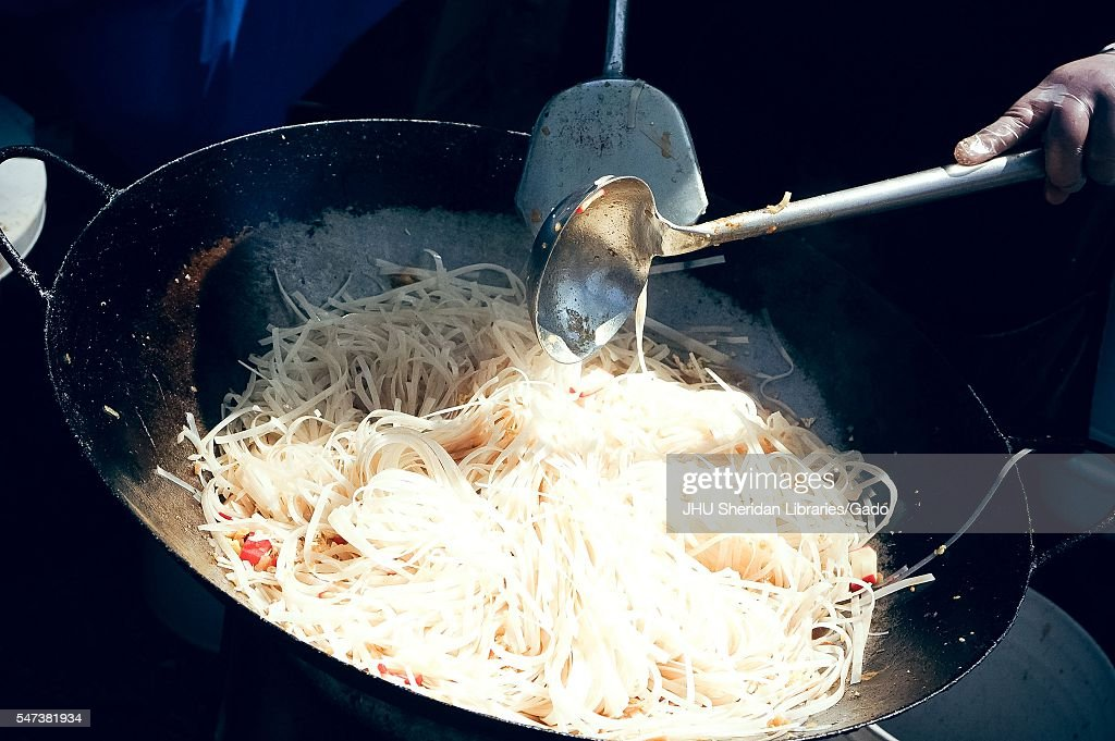 A worker's hand uses large metal spoons to stir a massive wok of stir-fry noodles, at a food booth during Spring Fair, a student-run spring carnival at Johns Hopkins University, Baltimore, Maryland, April, 2016. Courtesy Eric Chen. (Photo by JHU Sheridan Libraries/Gado/Getty Images).