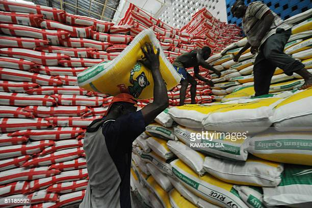 Workers handle sacks of imported rice on May 21 2008 at a warehouse in Abidjan According to Koffi Ahoutou president of the interministerial committee...