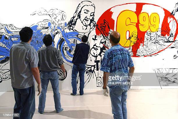 Workers hang a canvas of American artist Andy Warhol 26 January 2005 in the Lyon Contemporary Art Museum The Late Work on display in Lyon from 28...