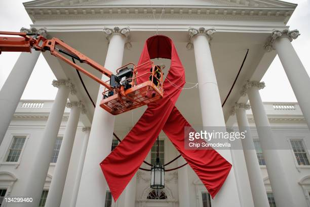 Workers hang a huge red ribbon on the North Portico of the White House one day ahead of World AIDS Day November 30 2011 in Washington DC The day was...