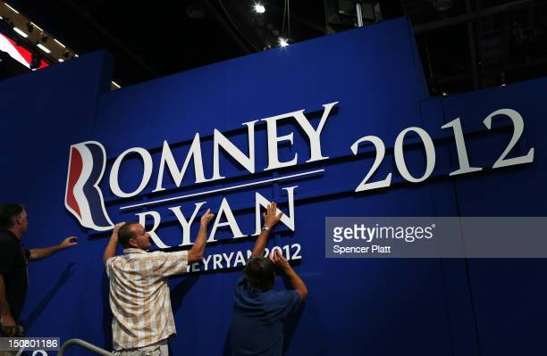 Workers hang a sign ahead of the Republican National Convention at the Tampa Bay Times Forum on August 26 2012 in Tampa Florida The RNC is scheduled...