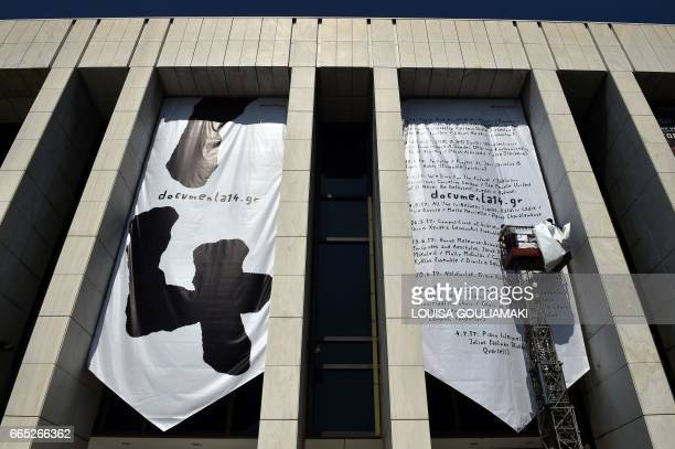 Workers hang banners at a concert hall in Athens concerning the 14 Documenta contemporary arts exhibition prior a press conference and preview for...