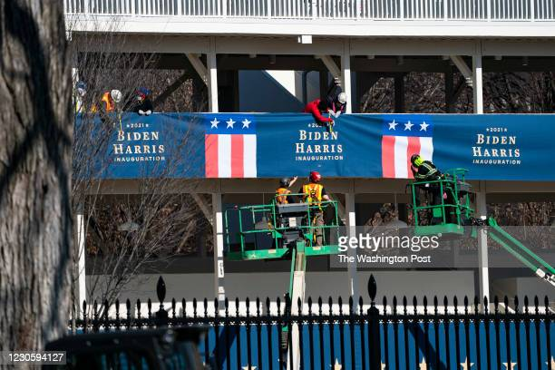 Workers hang banners for President-Elect Biden and Vice President-Elect Kamala Harris ahead of the inauguration on a press riser just outside the...