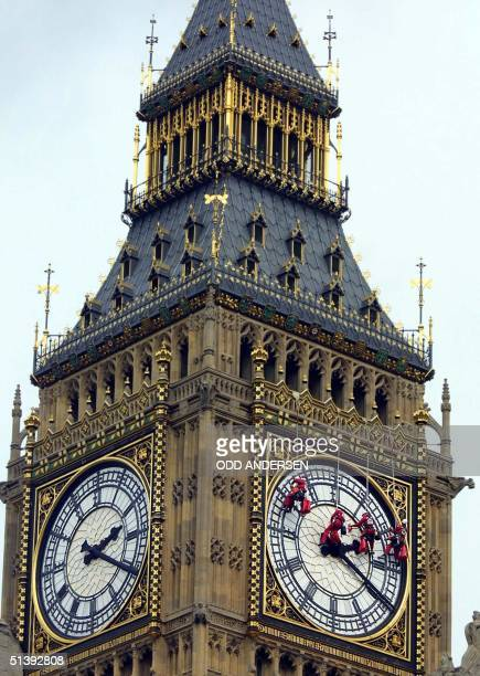 Workers hang from wires 20 August 2001 as they clean the London landmark clock tower Big Ben at the parliament in central London. AFP PHOTO / Odd...
