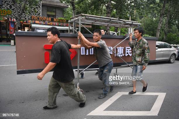 Workers haul a new sign for a supermarket along a street in Beijing on July 13 2018 China is expected to announce that the world's secondlargest...