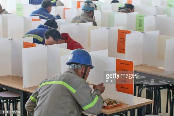 Workers have lunch at a dining hall using boards to separate people to prevent the spread of the new coronavirus in Yantai in China's eastern...