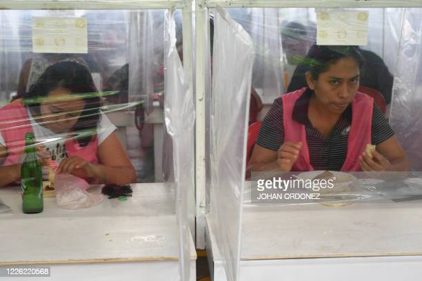 Workers have lunch separated by plastic panels as a preventive measure against the spread of the novel coronavirus COVID19 at the textile plant...