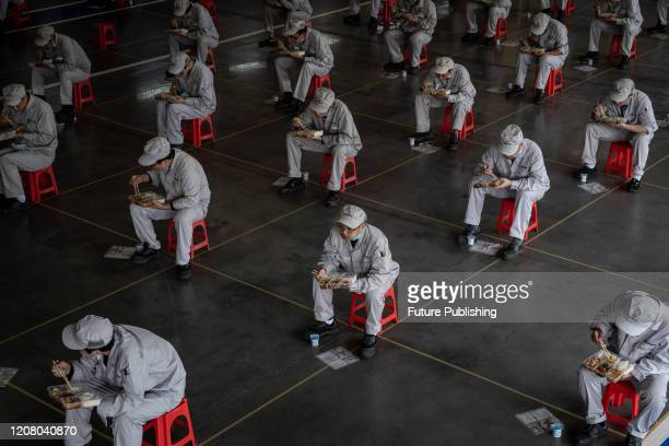 Workers have lunch with 15 meters away from others at the jointventure Dongfeng Honda in Wuhan in central China's Hubei province Monday March 23 2020...