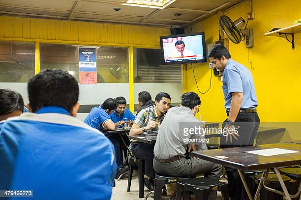 Workers have their morning tea as a news report showing Hishammuddin Hussein, Malaysia's acting transport minister, is broadcast on a television...