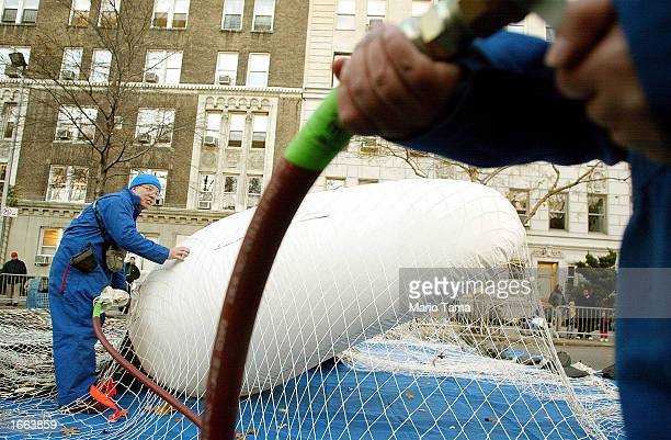 Workers help inflate a giant Clifford the Big Red Dog helium balloon in preparation for the Macy's Thanksgiving Day Parade November 27, 2002 in New...