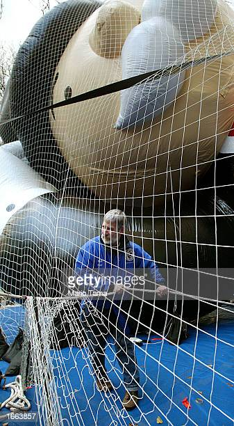 Workers help inflate a giant Mr. Monopoly helium balloon in preparation for the Macy's Thanksgiving Day Parade November 27, 2002 in New York City....