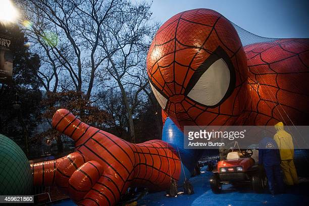 Workers help inflate balloon floats with helium in preparation for the annual Macy's Thanksgiving Day Parade on November 26 2014 in New York City The...