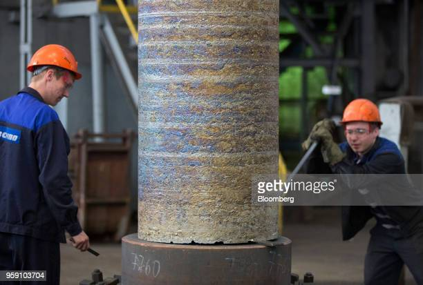 Workers help position a large ingot of titanium alloy after melting in a vacuum arc furnace at the VSMPOAVISMA Corp plant in Verkhnyaya Salda Russia...