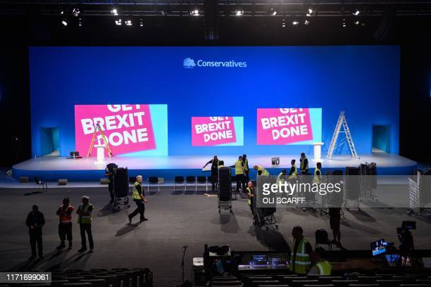 Workers help prepare an auditorium with Conservative Party branding inside Manchester Central convention centre the venue of the annual Conservative...