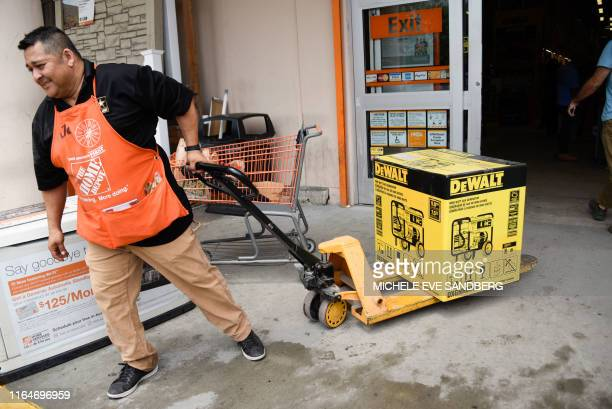 Workers help residents at Home Depot where they are buying generator equipment and other supplies on August 29 as they prepare for Hurricane Dorian...