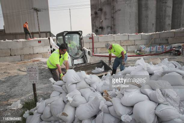 Workers help to construct a temporary floodwall along Highway 100 to keep floodwater from the Mississippi River out of the historic downtown area on...