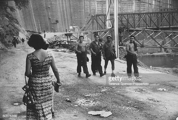 Workers helping in the construction of the Kariba Dam looking at a passing woman.